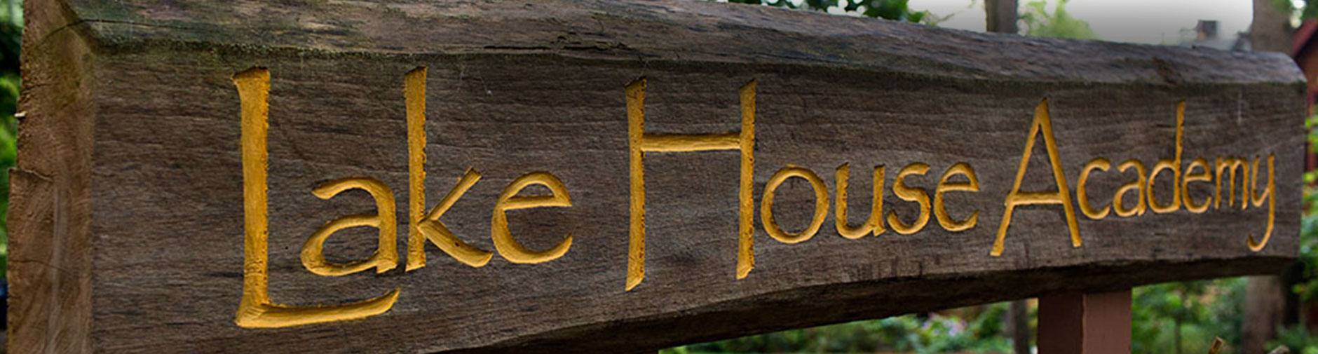 Wooden welcome sign at Lake House Academy
