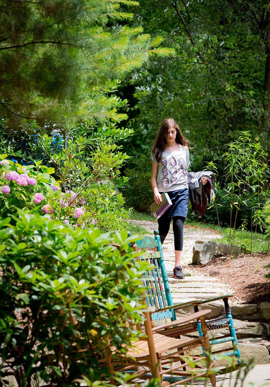 Girl with book walking path at Lake House Academy